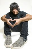 picture of emo-boy  - Sitting teenage boy making heart symbol with hands - JPG