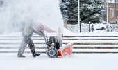 Snow-removal Work With A Snow Blower. Man Removing Snow. Heavy Precipitation And Snow Piles poster