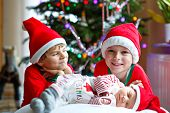 One Week Old Newborn Baby Girl And Two Siblings Kid Boys In Santa Claus Hats Near Christmas Tree Wit poster