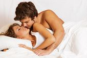 stock photo of kissing couple  - Young beautiful couple kissing in bed - JPG