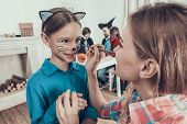 Mother Helping Daughter With Costume For Halloween. Adult Woman Putting On Makeup On Smiling Young G poster