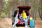 Happy Young Family Near Car Trunk Loaded With Suitcases Outdoors poster