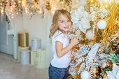 Little Girl Decorating Christmas Tree On Christmas Eve At Home. Young Kid In Light Bedroom With Wint poster