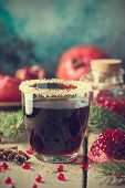 A Glasses Of Pomegranate Juice With Fresh Pomegranate Fruits And Fir Tree Branches On Wooden Table.  poster