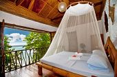 foto of canopy  - Rural style bedroom with canopy bed with sea view - JPG