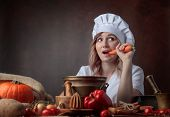 Young Beautiful Girl In A Chefs Uniform Eating Carrots. poster