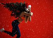 Sexy Christmas Fitness Sport Woman Wearing Santa Hat Holding  Xmas Tree On Her Shoulders. Running Fo poster