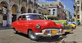 Old american classic cars parked in a street of havana city with crumbling buildings in the backgrou