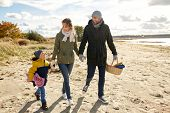 family, leisure and people concept - happy mother, father and little son walking along autumn beach  poster