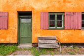 Street Bench At Front Of Colorful House. Facade Of Historical Brick Building In Copenhagen, Denmark. poster
