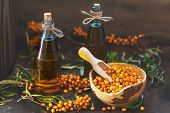 Natural, Organic Sea-buckthorn Berry In Bowl And Sea Buckthorn Oil In Glass Vintage Bottle poster
