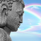 Face of a Buddha with eyes closed in prayer, with a blue sky and double rainbow in reflection in the