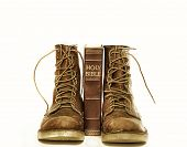 stock photo of boot  - Rugged boots and bible isolated against white - JPG