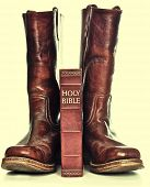 stock photo of love hurts  - Rugged cowboy boots and bible - JPG