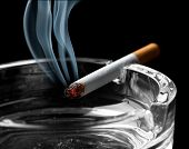 Closeup of cigarette on ashtray with a beautiful wisp of smoke