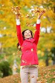 Happy fall woman throwing autumn leaves up in the air smiling blissful and cheerful in autumn forest