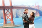 Golden gate bridge happy travel couple in San Francisco, USA smiling at camera. Young interracial hipster couple enjoying the view at the famous travel landmark. poster