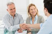 stock photo of contract  - Senior Happy Couple Shaking Hand With Financial Advisor - JPG