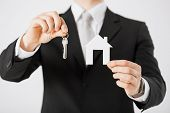stock photo of possession  - man hand holding house keys and paper house - JPG