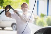 image of pressure-wash  - Bald man with a beard is washed with a pressure washer on a sunny day - JPG