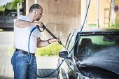 picture of pressure-wash  - Bald man with a beard is washed with a pressure washer be black car - JPG