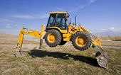 picture of earth-mover  - yellow earth mover rising on back and front scoop - JPG