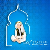 image of kareem  - Muslim boy reading Islamic religious holy book on blue background for Ramadan Kareem - JPG