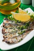 Grilled sardine wish served with lemon and herbs
