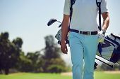 stock photo of caddy  - Golf player walking and carrying bag on course during summer game golfing - JPG