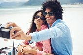 stock photo of windy  - couple taking selfie self portrait at the beach with retro hipster camera - JPG
