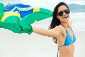 Latino woman with Brasil flag laughing and smiling in support of Brazilian soccer fan
