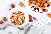 picture of toffee  - Many toffee on plate and in bowl on napkin on board on wooden table - JPG
