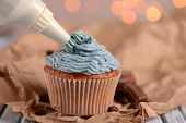 Confectioner decorating tasty cupcake with butter cream, on color wooden table, on lights background