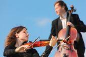 Постер, плакат: Скрипач и виолончелист играть против неба