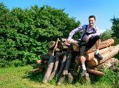 stock photo of lederhosen  - Young man wearing traditional Bavarian lederhosen posing in countryside - JPG