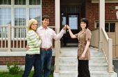 stock photo of real-estate agent  - Happy couple getting keys to new house from real estate agent - JPG