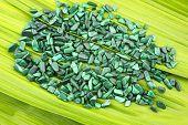 stock photo of malachite  - Bright green malachite stone pebbles on the leaf - JPG