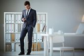 foto of sms  - Handsome businessman in suit and eyeglasses writing sms in office - JPG