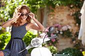 image of scooter  - Young beautiful italian woman sitting on a italian scooter - JPG