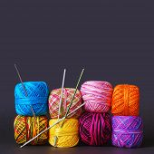 pic of coiled  - A tack of colorful yarn coils and needles over grey background - JPG