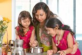 foto of indian sari  - Asian family cooking food together at home - JPG