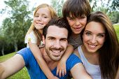 image of selfie  - Summer scene of Happy young family taking selfies with her smartphone in the park - JPG