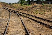 foto of merge  - Old overgrown used railway tracks intersection that merge - JPG