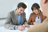 picture of rental agreement  - Young couple in real estate agency signing property agreement - JPG