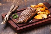 picture of cutting board  - Well done grilled New York steak with roasted potato wedges on cutting board on dark wooden background - JPG