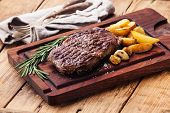 picture of ribeye steak  - Medium rare grilled Beef steak Ribeye with roasted potato wedges on cutting board on dark wooden background - JPG