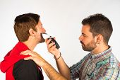 stock photo of barber razor  - Barber trimming a beard with an electric razor - JPG