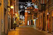 picture of cobblestone  - Evening view of cobblestone street in old town of Alba with illuminations and decorations for Christmas and New Year celebrations in Piedmont - JPG