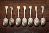 foto of tablespoon  - a row of vintage silver tablespoons with patina and scratches against grunge wood background - JPG