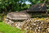 picture of old stone fence  - Mossy stone fence and old boat as decoration - JPG